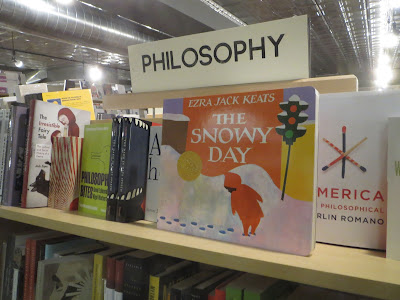 Picture book The Snowy Day sitting on a shelf of books labeled Philosophy