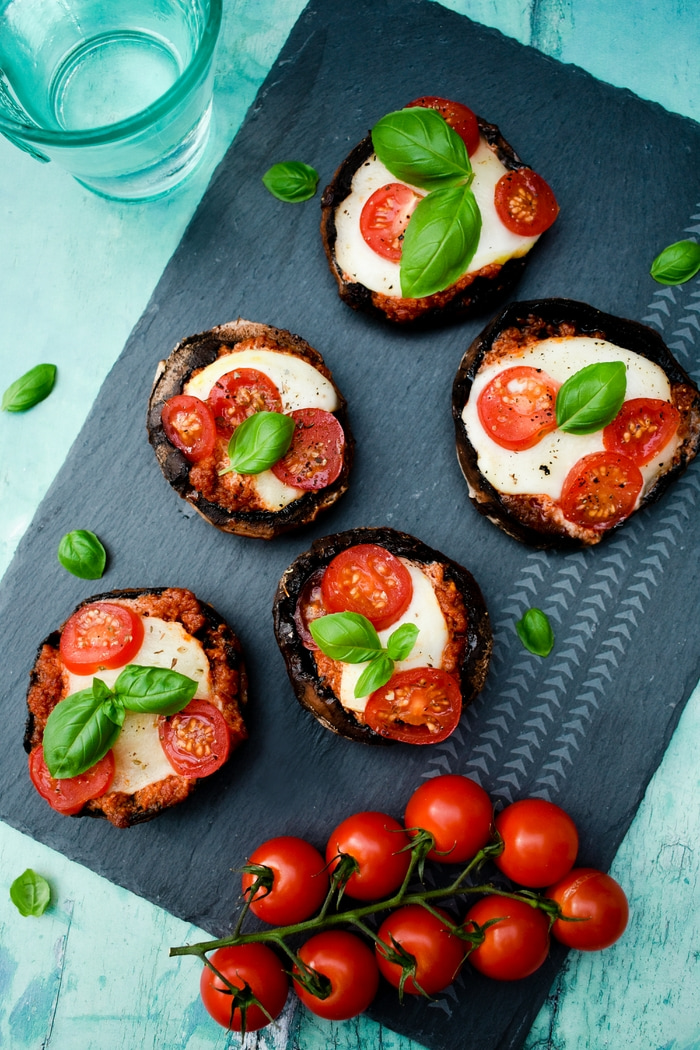 BBQ Pizza Stuffed Mushrooms on a black slate board with fresh cherry tomatoes