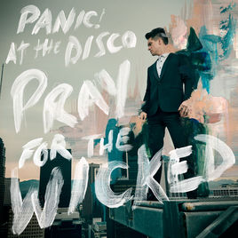A man in a black tux with quiffed black hair on a white platform posing into the distance on a grey background with Pray For The Wicked in drippy white font on a bright background.