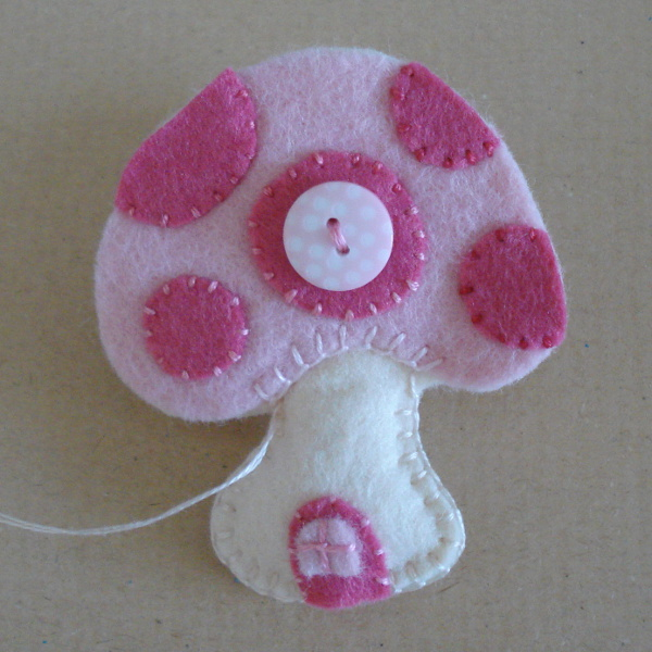 Sewing around pink toadstool home by hand blanket stitch