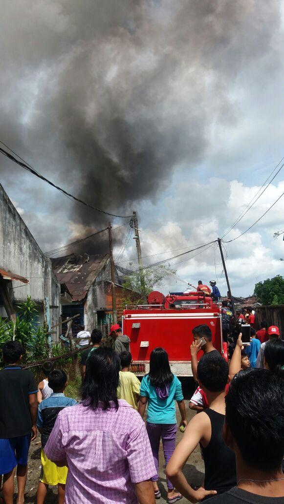 Warga menyaksikan petugas pemadam kebakaran yang sedang memadamkan api.