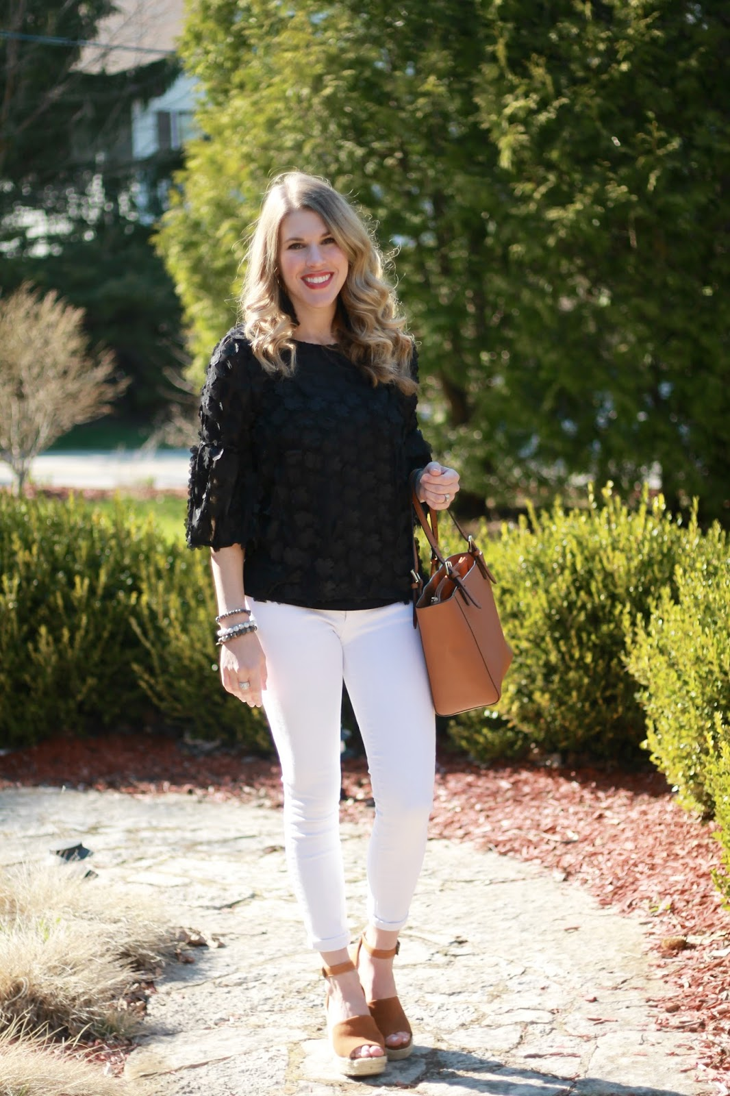 black floral applique top, white jeans, cognac wedges, cognac leather tote