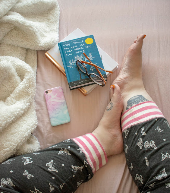 legs in black pyjamas with white butterflies on pink sheet with books, glasses and phone