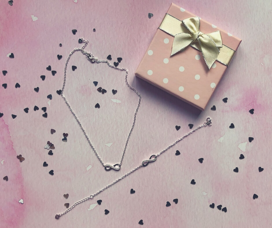 "A silver necklace and bracelet with an infinity symbol that is encrusted with cubic zirconia stones sits on top of a pink background surrounded by small silver hearts. Image for ""Beautiful jewellery from Kaya Jewellery & WIN £40 voucher!"""