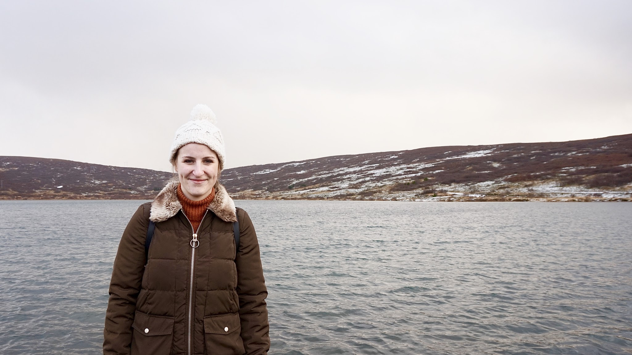 smiling woman in a bobble hat in front of a lake