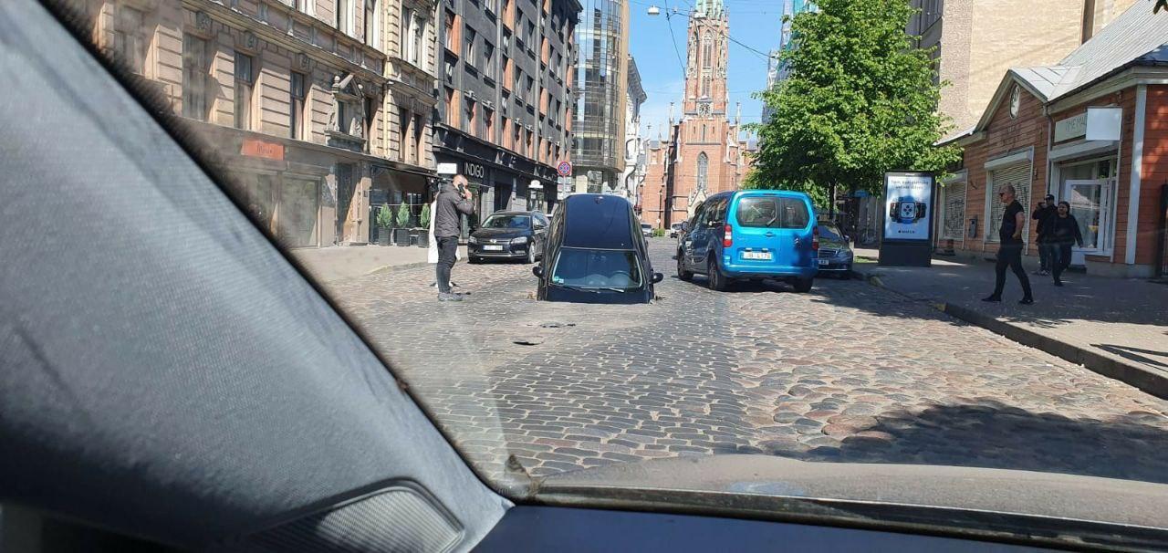 Vīrietis zvana pa tālruni pie ceļa bedrē iebraukušas mašīnas