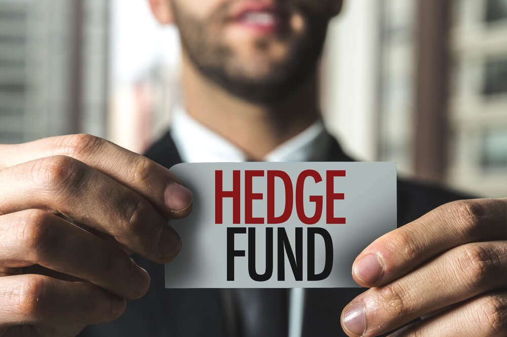 hedge funds written on a card held by a man in suit