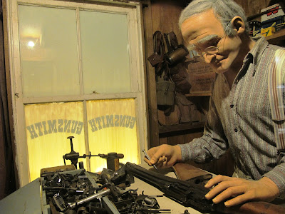 Full-scale model of the interior of an early 20th century gunsmith's shop, with a man working on a gun.