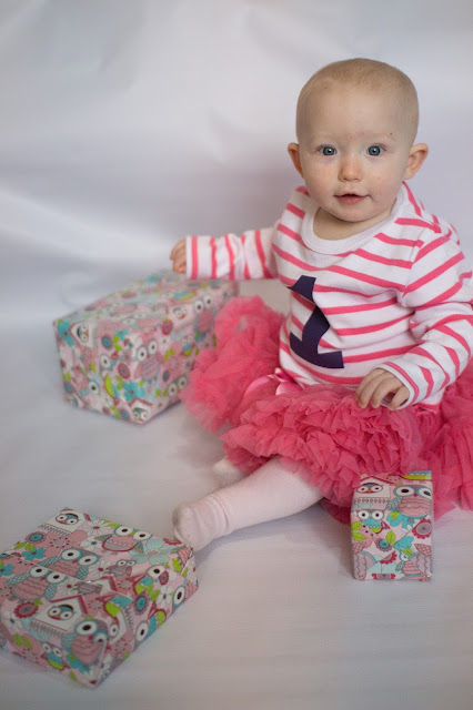 A one year old girl in a pink skirt and white and pink striped top (same as above picture) with 3 presents