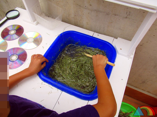 Niño removiendo agua y césped en una cocinita de exterior