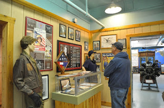 Man looking at a museum display about Women Air Service Pilots