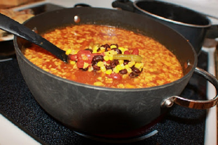 this is a bowl of southwest style chili or you can make it into a southwest soup. It is in a square bowl with beans, tortilla, cheese melted , tomatoes, green chilies, green beans, corn and chicken.