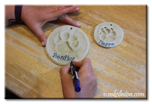 Using paint pen to write dog's names on salt dough paw print keepsake