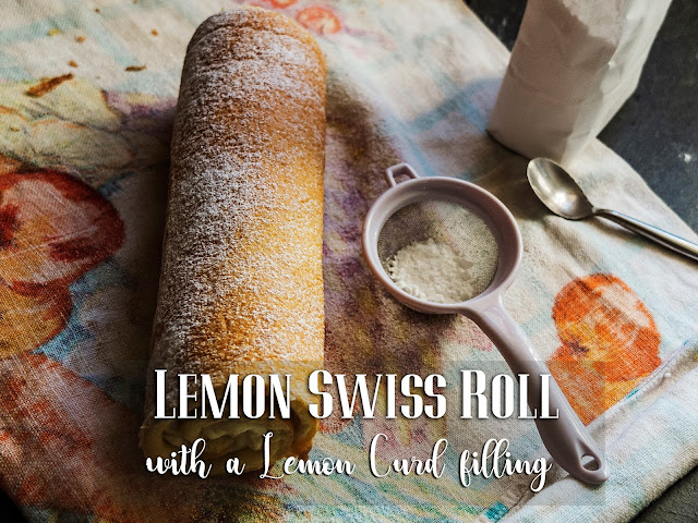 A lemon swiss roll dusted with icing sugar lying on a tea towel with a sieve.