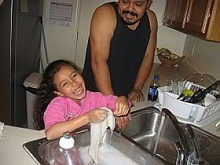 A young daughter helping her dad to wash dishes