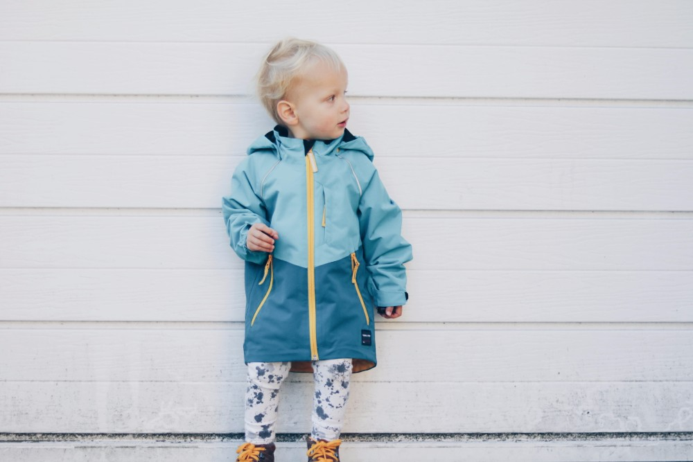 toddler-boy-standing-in-front-of-white-garage-door-wearing-a-blue-coat