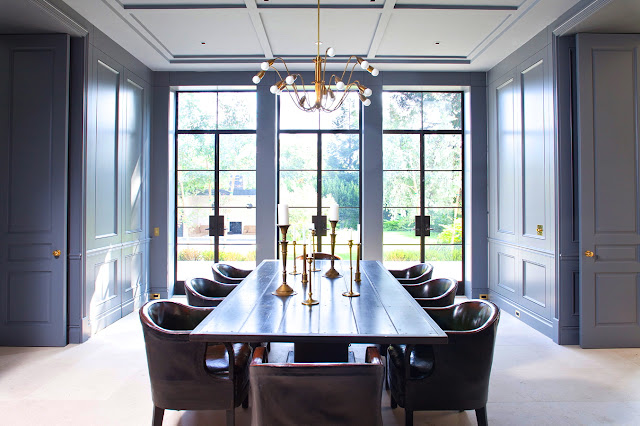 formal dining room with steel painted paneled walls, white coffered ceilings and brass accents