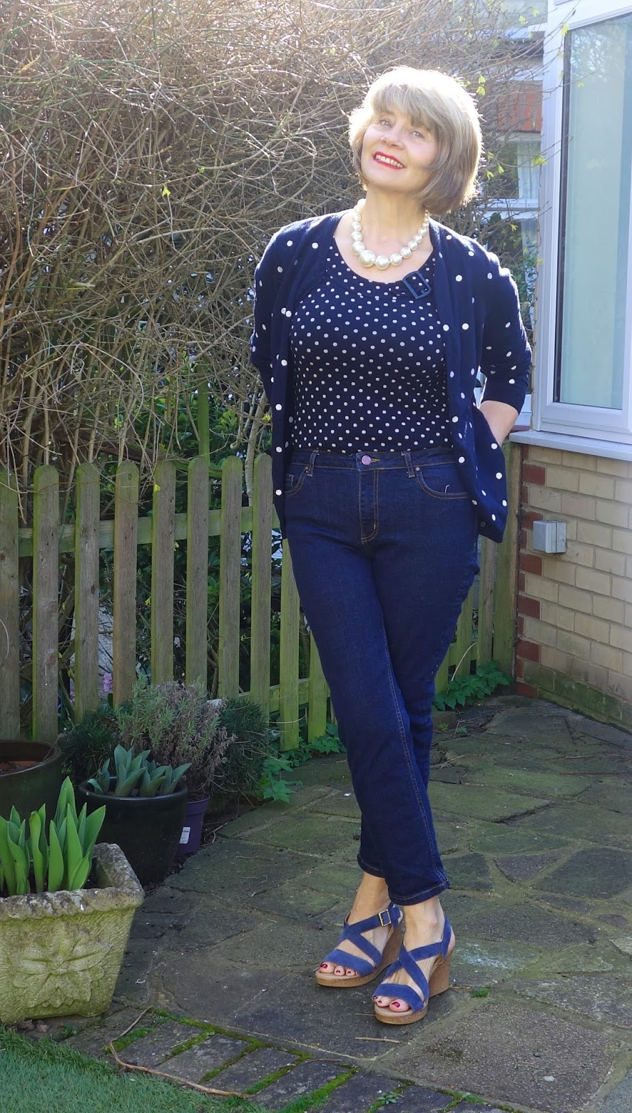 Image showing outfit featuring polka dots: jeans, cardi, wedge heels, pearls.
