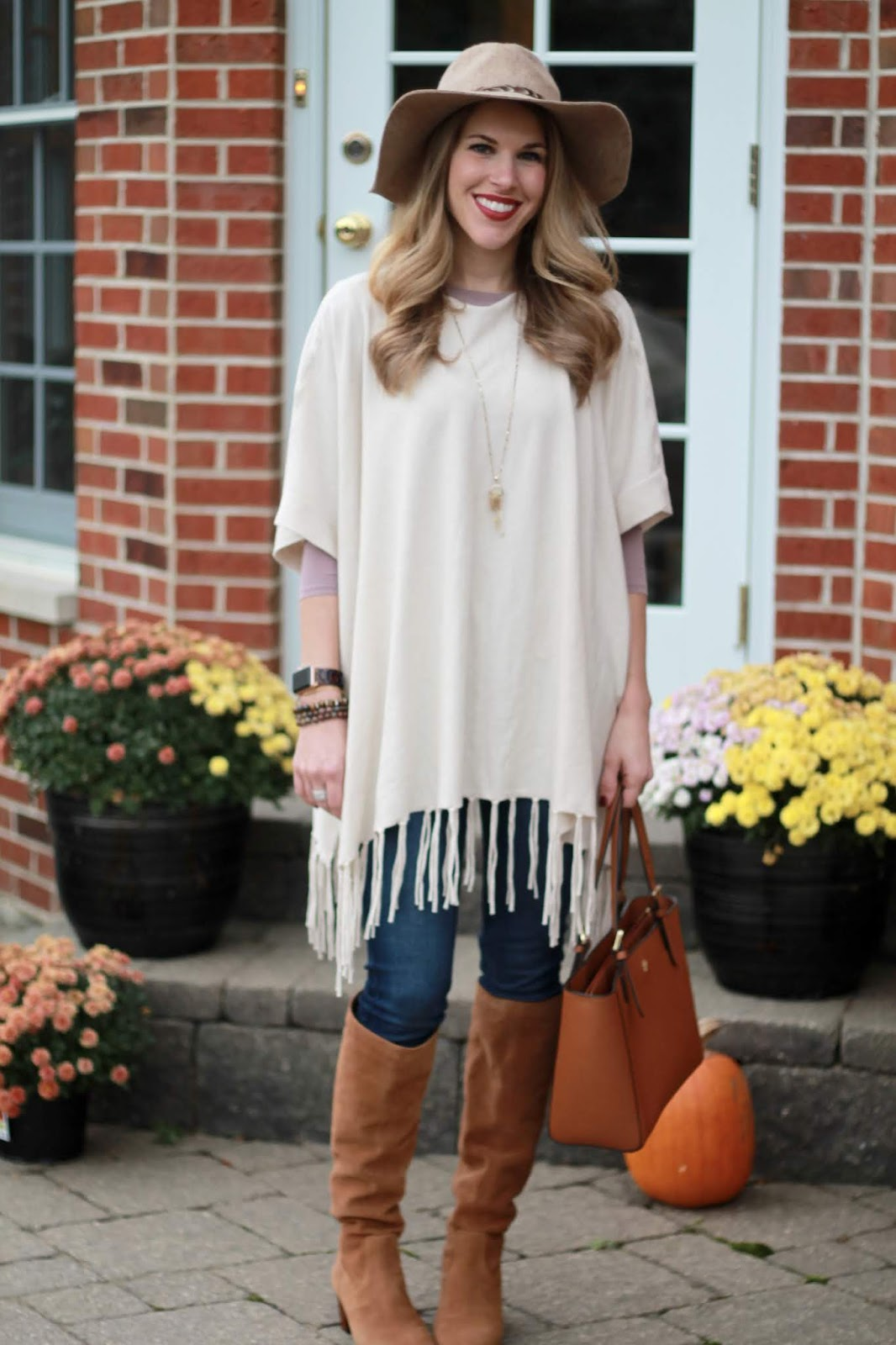 Ivory fringe poncho, mauve long sleeve tee, skinny jeans, cognac slouchy boots, Tory Burch cognac tote, wide brim fedora