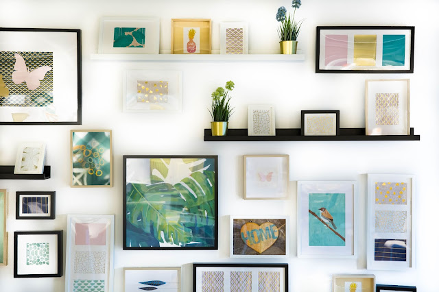 Wall covered in frames pieces of art, prints and paintings