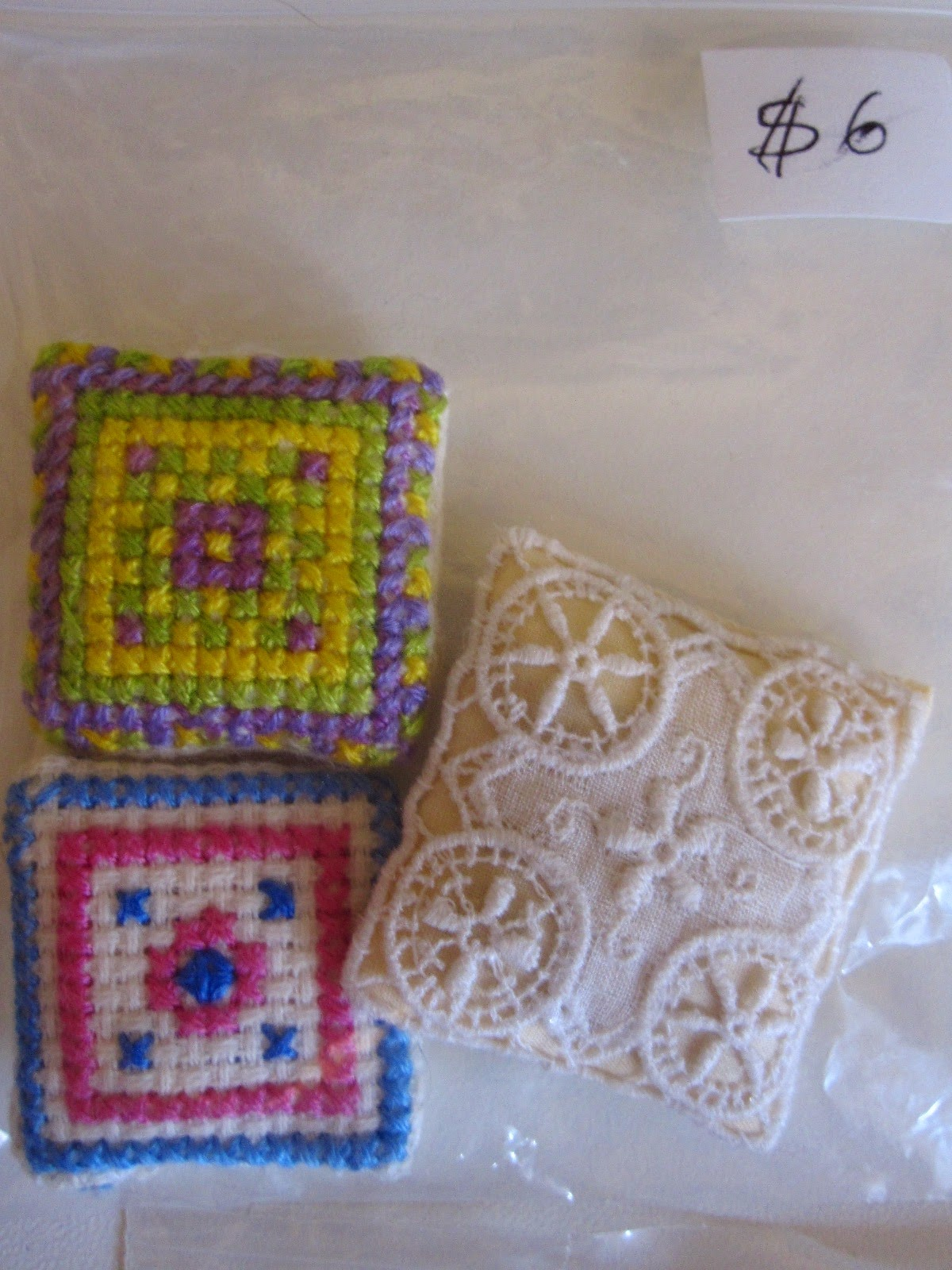 Bag with three dolls' house miniature cushions, two cross stitched, one is lace. Bag is priced at $6.