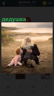 На песке около водоема сидят дедушка и ребенок, смотрят в сторону
