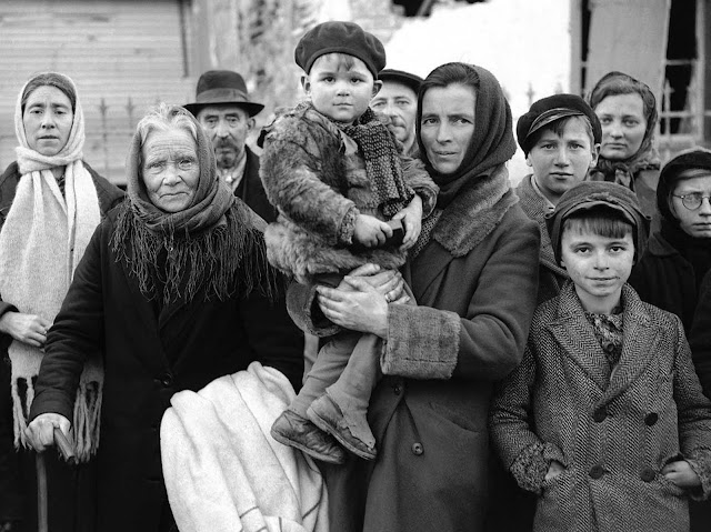 Refugees stand in a group in a street in La Gleize, Belgium on January 2, 1945, waiting to be transported from the war-torn town after its recapture by American Forces during the German thrust in the Belgium-Luxembourg salient.