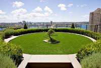 Bir binanın üst teras katındaki yuvarlak, çimen bahçeli ve bonsai ağaçlı peyzaj çalışması