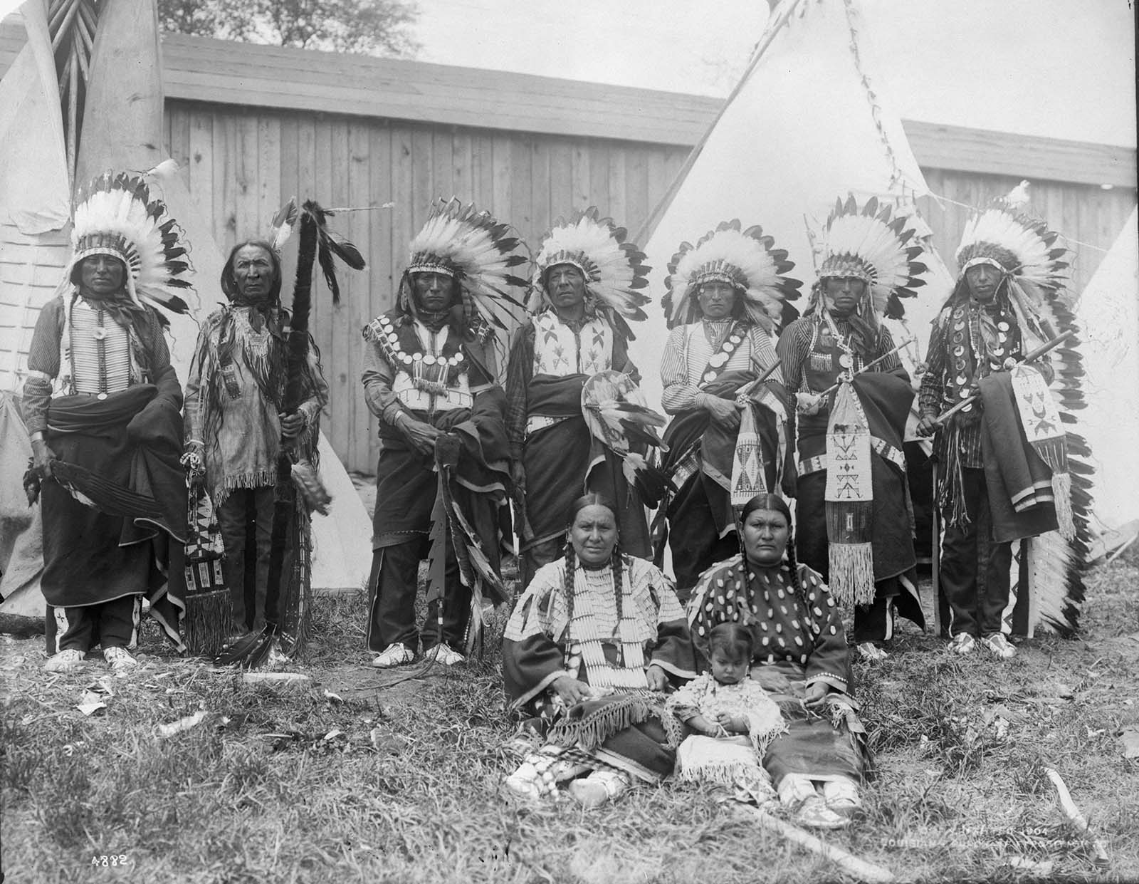 Chief Yellow Hair and his council standing in front of replicas of teepees at a human zoo at the 1904 World's Fair in St Louis, Missouri.