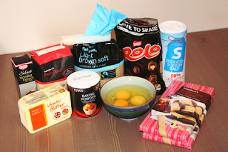 ingredients for cookie dough bars on a table; vanilla extract, butter, flour, light brown sugar, rolo bites, 3 eggs in a bowl, reduced sodium salt, and two bars of plain cooking chocolate