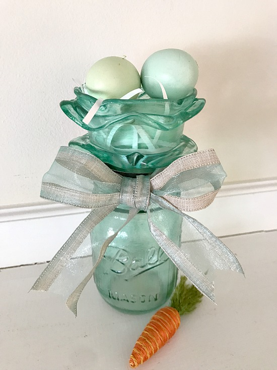 blue frosted Mason Jar with eggs in nest on top