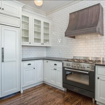 white swbuay tiles, white cabinets, black verona stove and overlay fridge