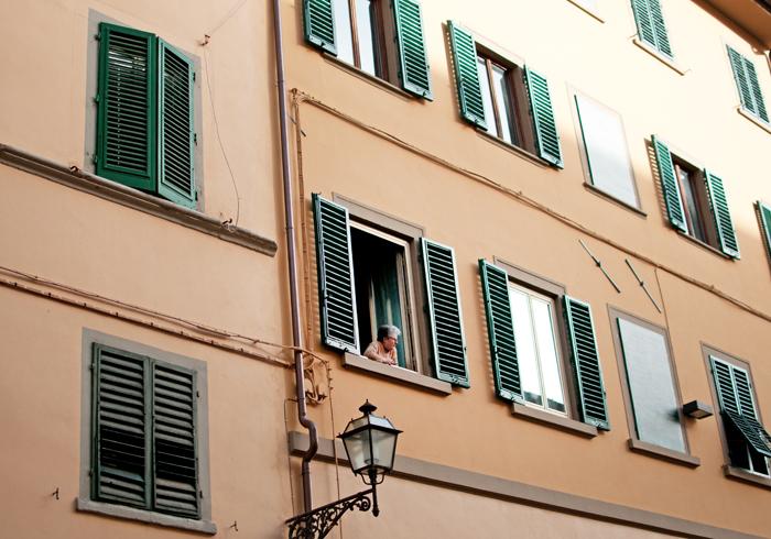 Vue d'une façade d'immeuble. A une fenêtre, une femme regarde dans la rue