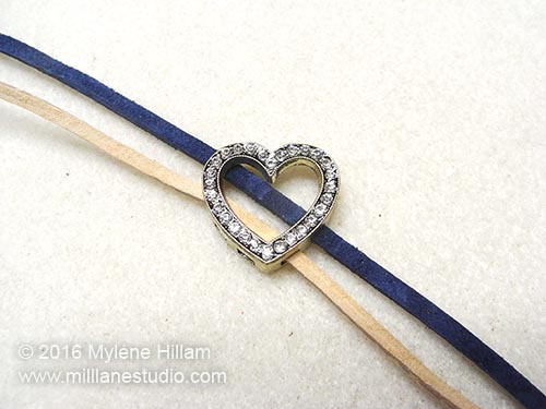 Sandy Beach leather lace is strung through the heart slider diagonally alongside the Cadet Blue lace.