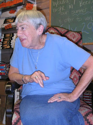 Author Ursula Le Guin sits in a chair in this photo.