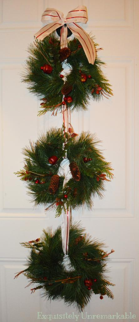 Triple Christmas evergreen wreath with candy cane ribbon on the door
