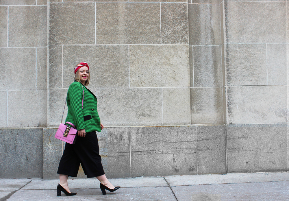 Image of blogger author Laura Kidd wearing a green blazer and black culottes walking down a downtown street.