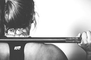 Mujer de espaldas con una barra sobre los hombros