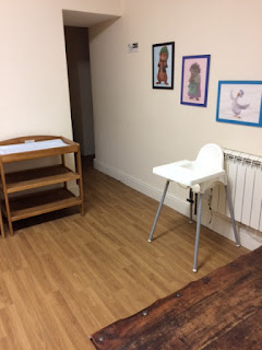 Room with changing table, highchair and pictures on the walls