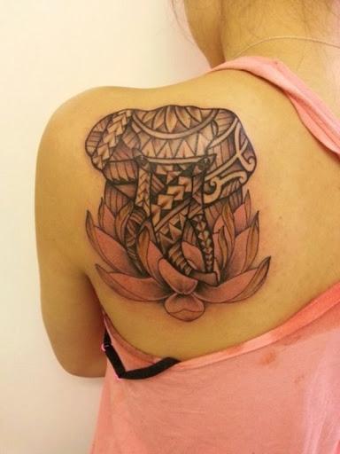 Estilizado elefante coberto em um design ornamentado fica no topo de uma rosa flor de lótus. Veja: 30 Incrível Desenho De Tatuagem De Flor De Lótus