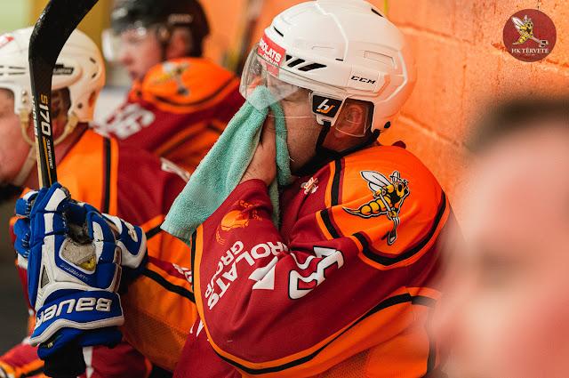 Hokejists ar dvieli slauka seju uz komandas soliņa