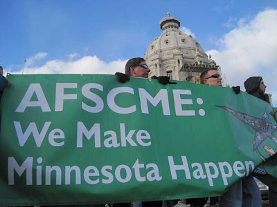 Several people holding a green AFSCME banner