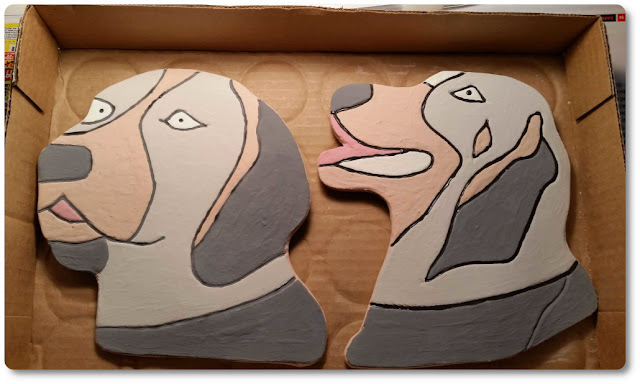 Clay dog heads before firing in the klin