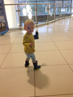 toddler holding one wellie and wearing the other