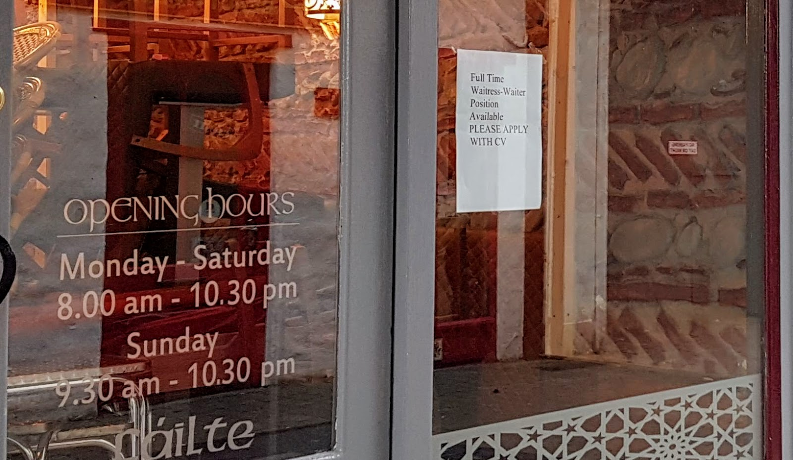 Job advert sign in Galway - along with Anfora restaurant opening hours and the word Fáilte in Irish script writing