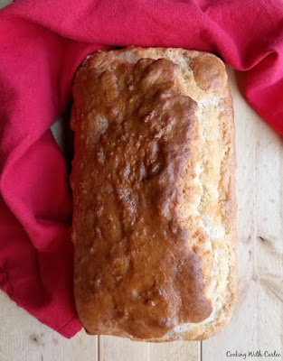 golden brown loaf of beer bread ready to be sliced