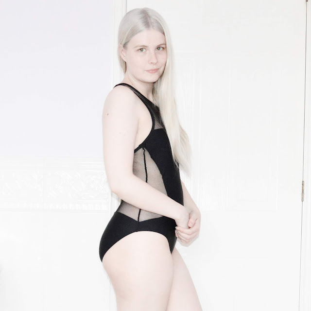 Blonde girl wearing black swimsuit
