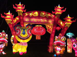 Pic of red Chinese Lantern arch and figures at entrance lit up at night
