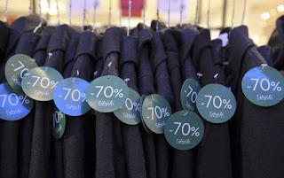 Vêtements étiquetés sur cintres et portants pour être vendus pendant les soldes