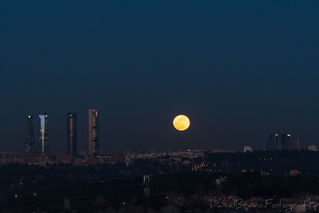 Fotografía de las 4 Torres de Madrid con la Luna llena de color naranja y la Puerta de Europa o Torres Kio